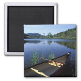Una canoa descansa sobre la orilla de poca charca  imán cuadrado
