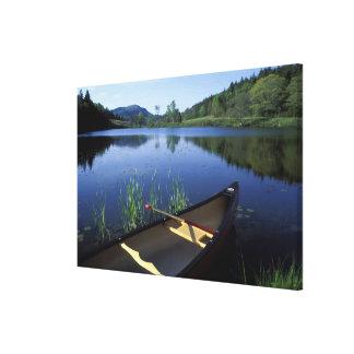 Una canoa descansa sobre la orilla de poca charca  impresiones en lona estiradas