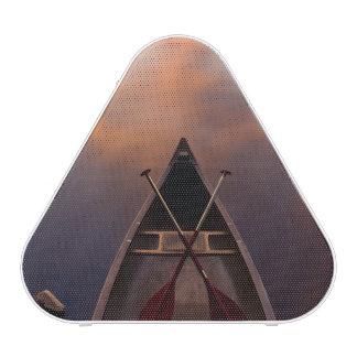 Una canoa descansa sobre la orilla del lago Pawtuc Altavoz Bluetooth