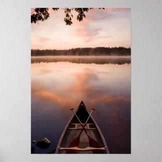 Una canoa descansa sobre la orilla del lago Pawtuc Póster
