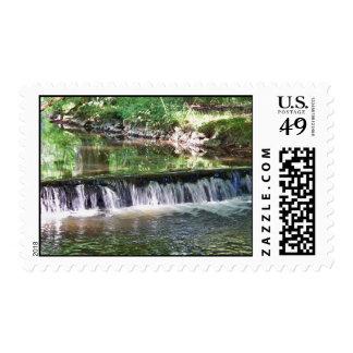 Una cascada apacible del río sello postal