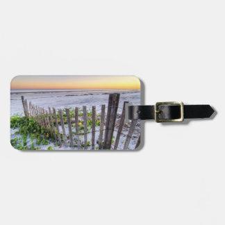 Una cerca de la playa en la puesta del sol etiquetas maletas