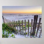 Una cerca de la playa en la puesta del sol póster
