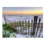 Una cerca de la playa en la puesta del sol tarjeta postal