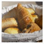 Una cesta de mimbre del desayuno con los croissant azulejo ceramica