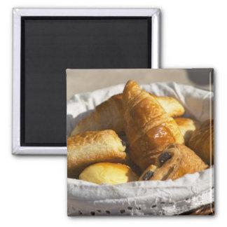 Una cesta de mimbre del desayuno con los croissant iman de nevera