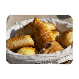 Una cesta de mimbre del desayuno con los croissant imanes flexibles
