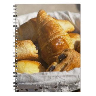 Una cesta de mimbre del desayuno con los croissant libretas espirales