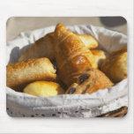 Una cesta de mimbre del desayuno con los croissant tapete de raton