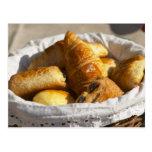 Una cesta de mimbre del desayuno con los croissant postal
