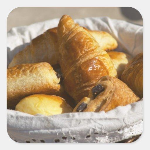 Una cesta de mimbre del desayuno con los pegatinas cuadradases