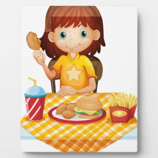 Una chica joven que come en el restaurante de placas de plastico