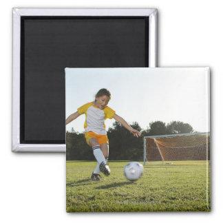 Una chica joven que juega a fútbol en un campo de imán cuadrado