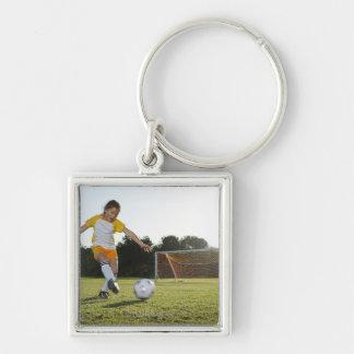Una chica joven que juega a fútbol en un campo de  llavero