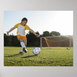 Una chica joven que juega a fútbol en un campo de  póster