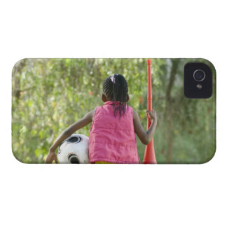 Una chica joven se sienta en un banco, sosteniendo Case-Mate iPhone 4 carcasas
