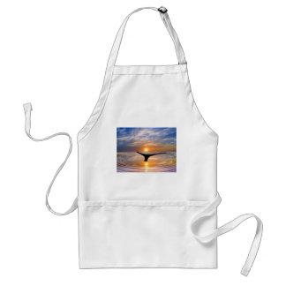 Una cola de las ballenas en la puesta del sol delantal