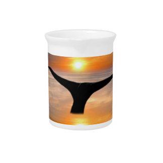 Una cola de las ballenas en la puesta del sol jarras para bebida