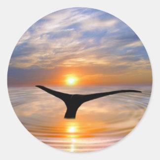 Una cola de las ballenas en la puesta del sol pegatina redonda