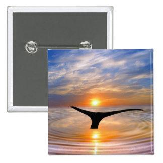 Una cola de las ballenas en la puesta del sol pins