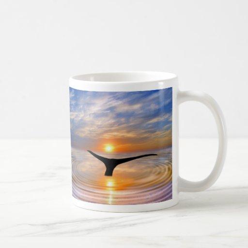 Una cola de las ballenas en la puesta del sol tazas