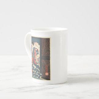 Una cortesana que fija su taza de la porcelana de  taza de porcelana