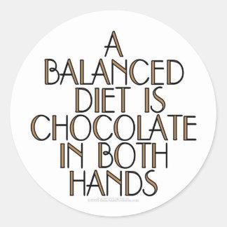 Una dieta equilibrada es chocolate en ambas manos pegatina redonda