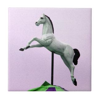 Una estatua del carrusel del caballo blanco contra azulejo cuadrado pequeño