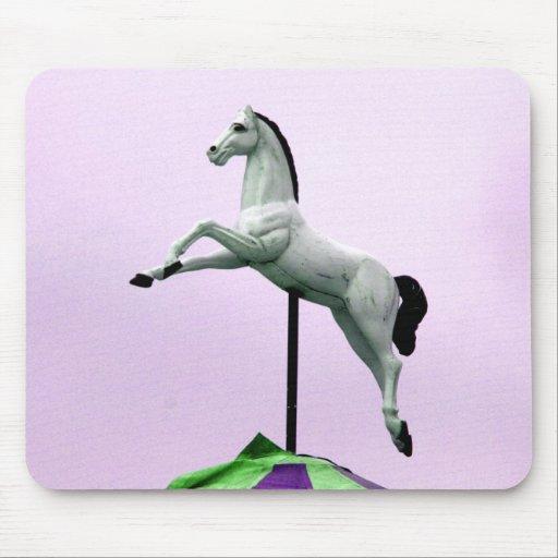 Una estatua del carrusel del caballo blanco contra tapetes de raton