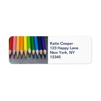 Una fila de lápices coloreados etiqueta de remite