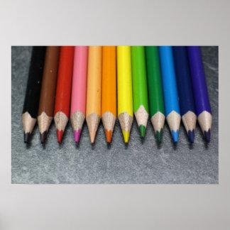 Una fila de lápices coloreados póster