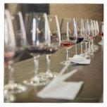 Una fila larga de copas de vino puso tan un grande azulejo cuadrado grande