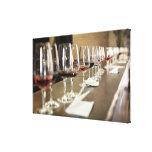 Una fila larga de copas de vino puso tan un grande lienzo envuelto para galerias