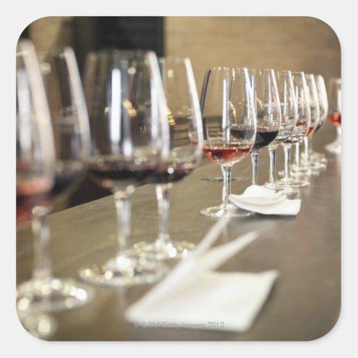 Una fila larga de copas de vino puso tan un grande pegatina cuadrada