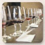 Una fila larga de copas de vino puso tan un grande posavaso