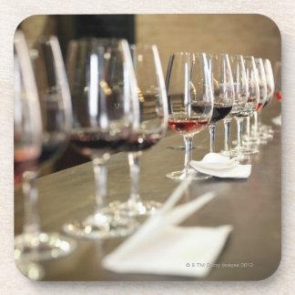 Una fila larga de copas de vino puso tan un grande posavasos de bebida