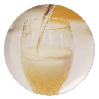 Una flauta de cristal del champán que es llenada d platos para fiestas