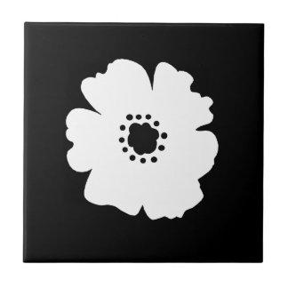 Una flor blanca intrépida en negro azulejo cuadrado pequeño
