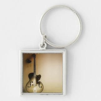 Una guitarra solitaria llavero cuadrado plateado