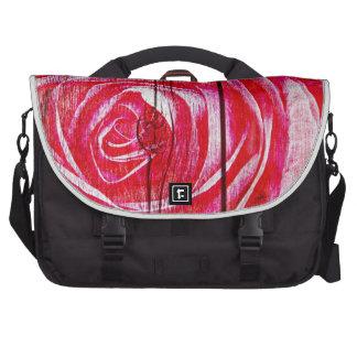 Una imagen color de rosa en un panel de madera suc bolsas para portátil