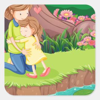 Una madre que abraza a su hija en el riverbank pegatina cuadrada