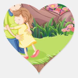 Una madre que abraza a su hija en el riverbank pegatina en forma de corazón