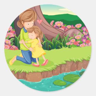Una madre que abraza a su hija en el riverbank pegatina redonda