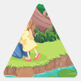 Una madre que abraza a su hija en el riverbank pegatina triangular