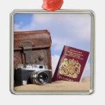 Una maleta de cuero vieja, una cámara retra y adorno navideño cuadrado de metal