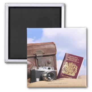 Una maleta de cuero vieja, una cámara retra y imán cuadrado