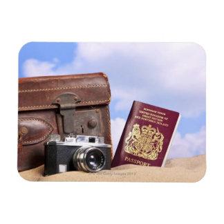 Una maleta de cuero vieja, una cámara retra y imán flexible