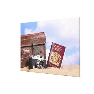 Una maleta de cuero vieja, una cámara retra y impresion en lona