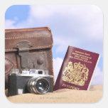 Una maleta de cuero vieja, una cámara retra y pegatina cuadrada