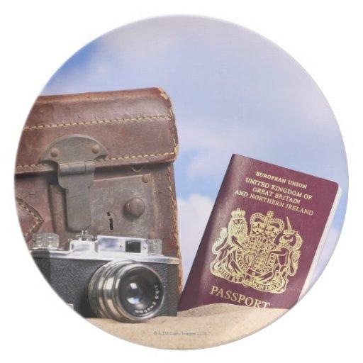 Una maleta de cuero vieja, una cámara retra y plato de cena